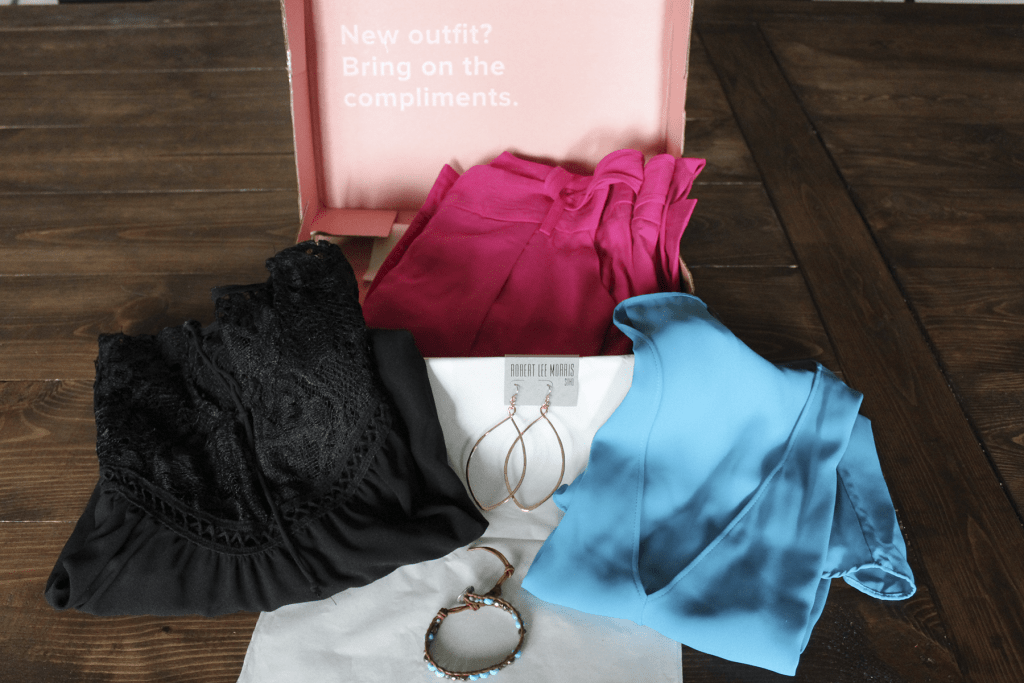 Le Tote Box with pink pants, blue sleeveless blouse, black peasant top, rose gold earrings, and leather wrap bracelet.