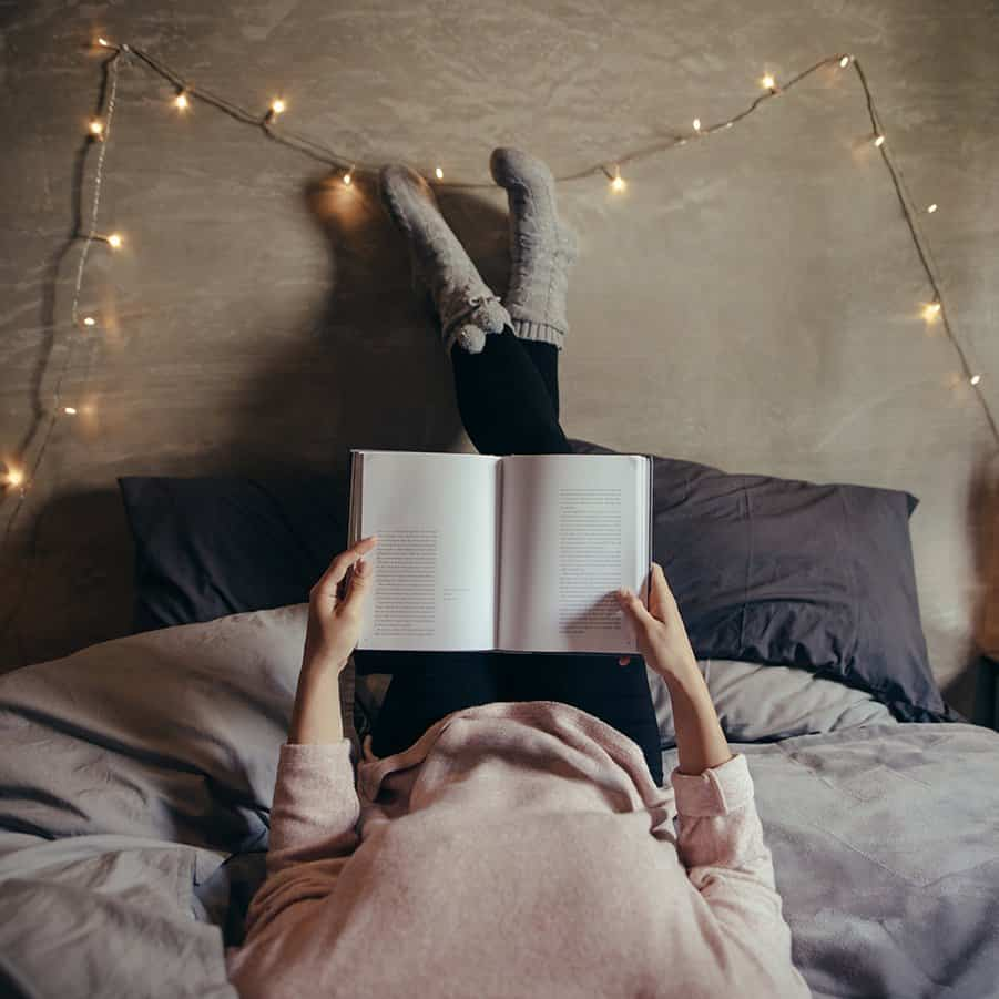Laying in cozy bed reading a book.  Best Books of 2019 - Top 10 Fiction & Top 10 Non-Fiction