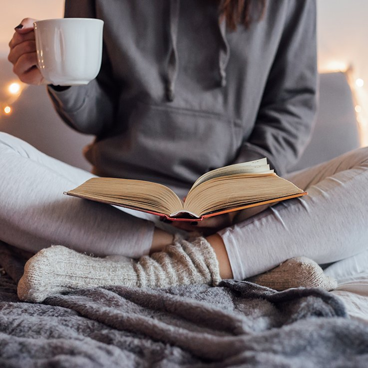 Woman Reading a Book with Coffee Mug - How to Read More: The Best Tips from Avid Readers